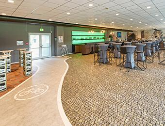 VIP Tribüne im Preussen Stadion mit FOTOBODEN™ in Objektqualität ausgestattet. Fahrradweg und Kopfsteinpflaster wurden individuell auf den Vinylboden gedruckt.