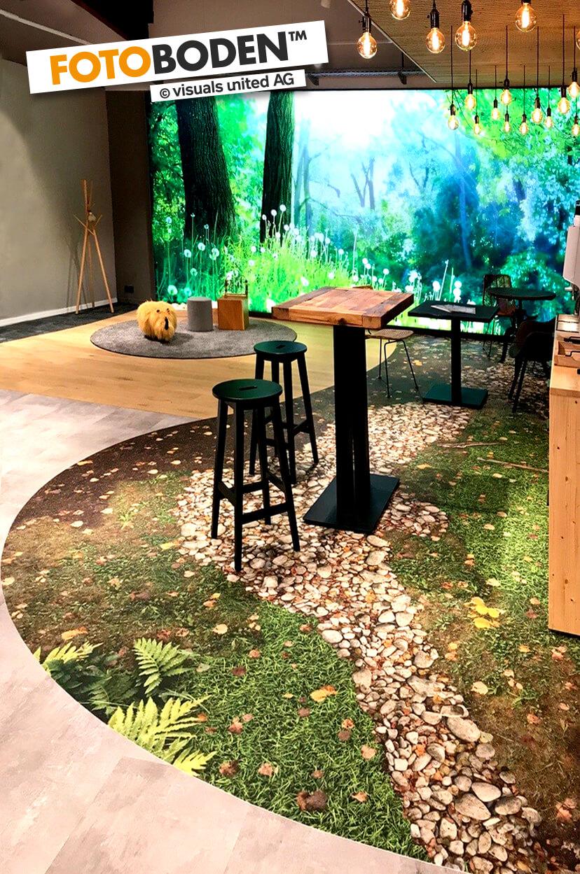 JOKA Citystore in Kassel. Waldboden aus FOTOBODEN™ in der Kaffeeecke für entspannte Beratungsgespräche.